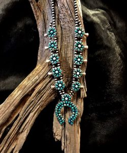 Beautiful squash blossom necklace with delicate cut stones, forming gorgeous squashes, and a horseshoe shaped naja.