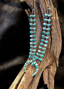 Beautiful Kingman turquoise squash blossom! Quality stones, in soft shades of aqua, form bow tie style side pieces! The Naja is very traditionally shaped, with soft variant hues of color.